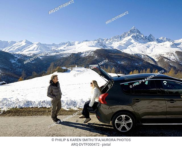 Couple of hikers rest on trunk of car near mountains