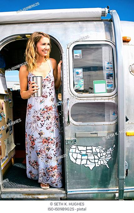 Young woman wearing maxi dress looking out from airstream doorway