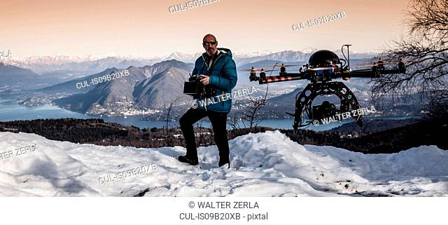 Mature man preparing to fly drone, Stresa, Piedmont, Italy