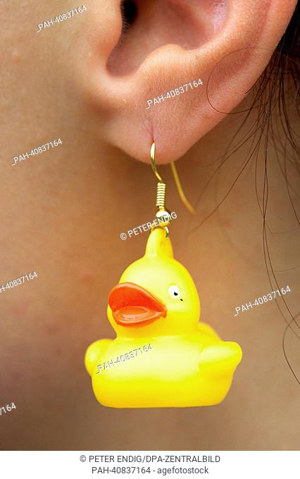 A woman wears rubber ducky earrings in Schlosspark Moritzburg in Zeitz, Germany, 05 July 2013. An exhibition featuring around 200 rubber duckies is on display...