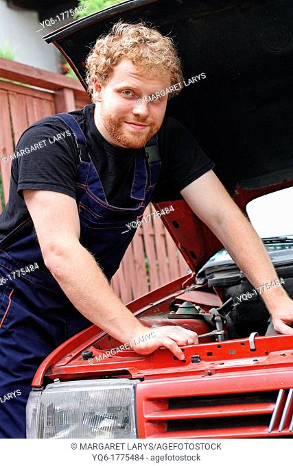 A young mechanic repairing the old car, portrait