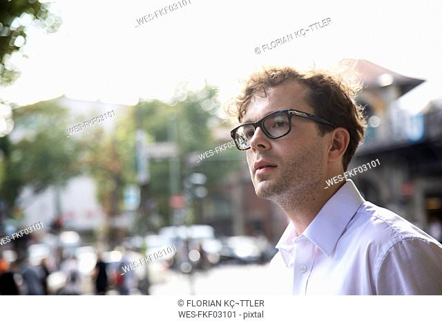 Germany, Berlin, portrait of businessman with stubble and glasses on the street