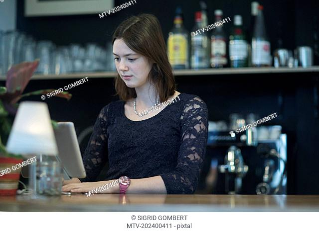 Young waitress using computer in coffee shop at checkout counter, Freiburg Im Breisgau, Baden-Württemberg, Germany