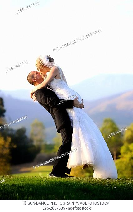 happy bride & groom kissing & embracing in scenic park