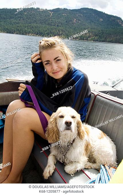 GIrl with her Cocker Spaniel, in a boat on a lake