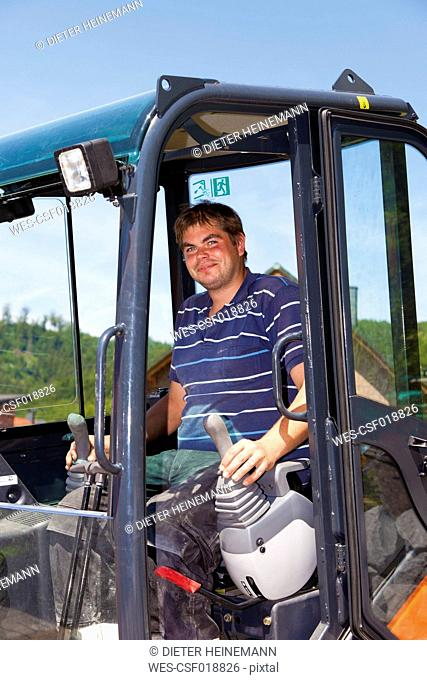 Germany, Rhineland Palatinate, Young man driving excavator