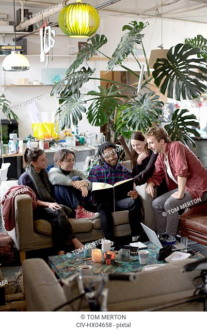 Young adult roommate friends reading book in apartment living room