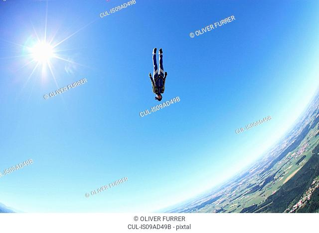 Female skydiver free falling head first above Leutkirch, Bavaria, Germany