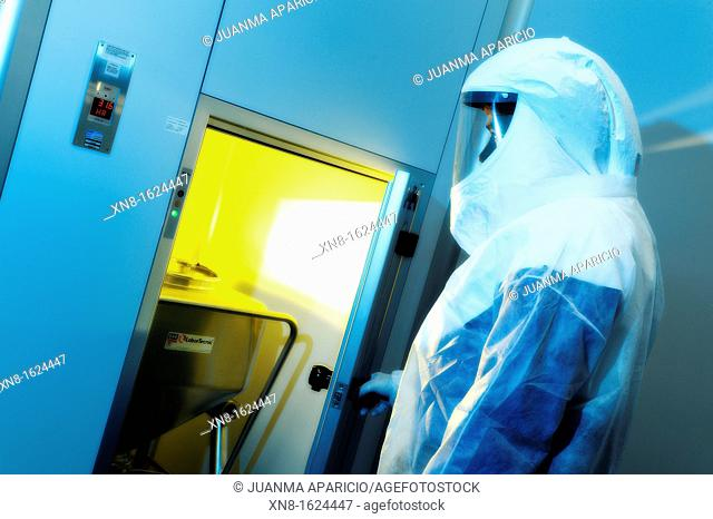 Laboratory technician equipped with Security Suit inside a technology lab photographed with spectacular lighths