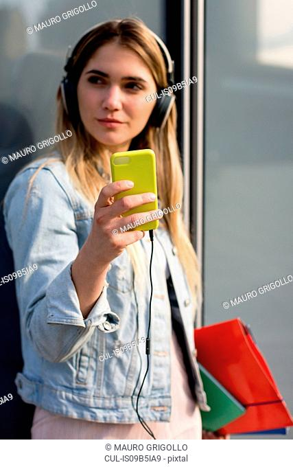 Young woman, outdoors, wearing headphones, taking selfie with smartphone