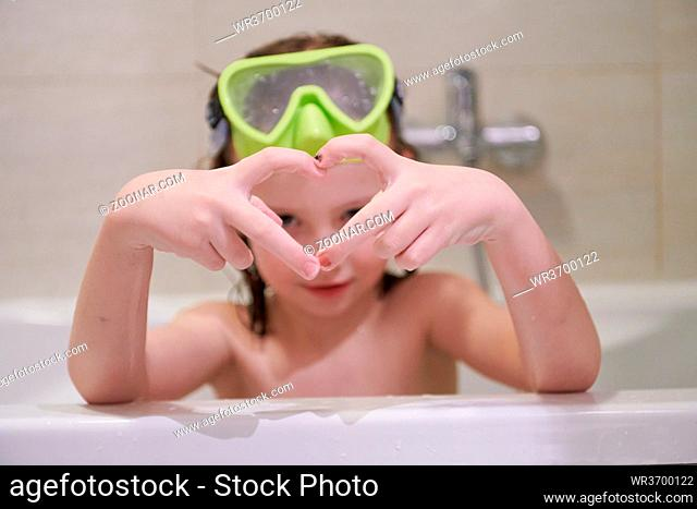 little girl with snorkel goggles in the tub while taking a bath in the bathtub, kids hygiene concept and summer vacation in corona virus stay at home