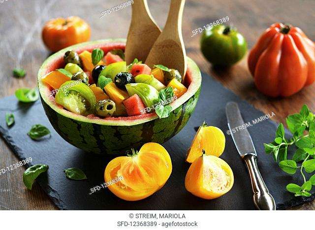 Culinary watermelon, filled with salad of watermelon, colorful tomatoes, olives and fresh herbs