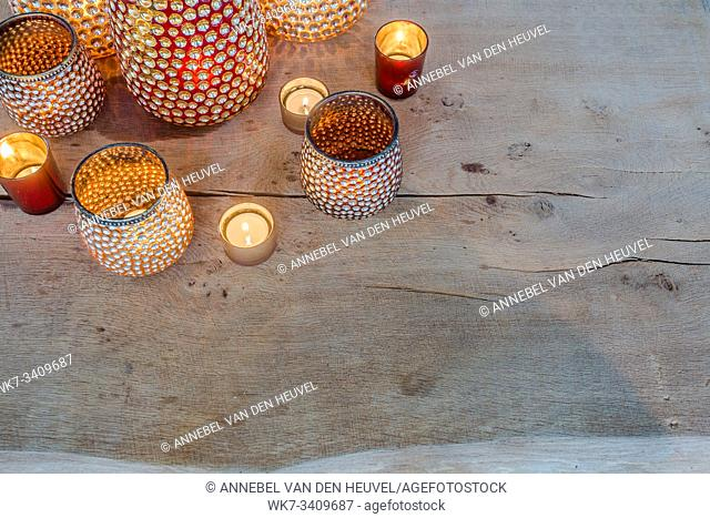 colorful orange candle holders on wooden table arabic design sparkles