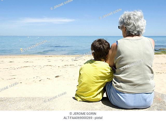 Grandmother and grandson sitting together on beach, looking at sea