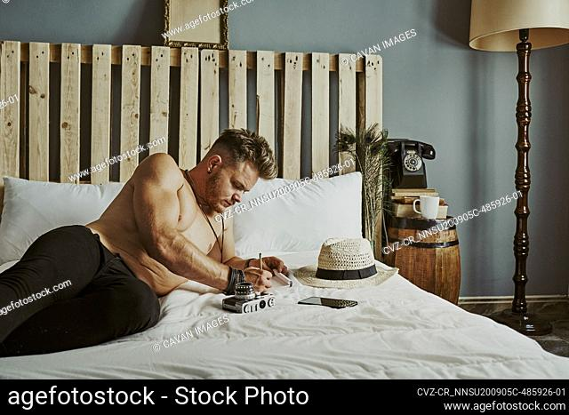 a young man lying in bed writing in a notebook