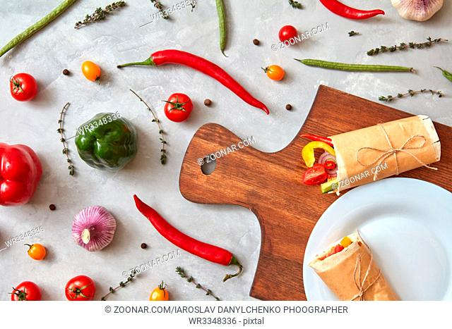 Vegetable burrito on a plate and on a wooden board, on a gray concrete background. Step-by-step recipe for cooking. Healthy food.Top view, flat lay