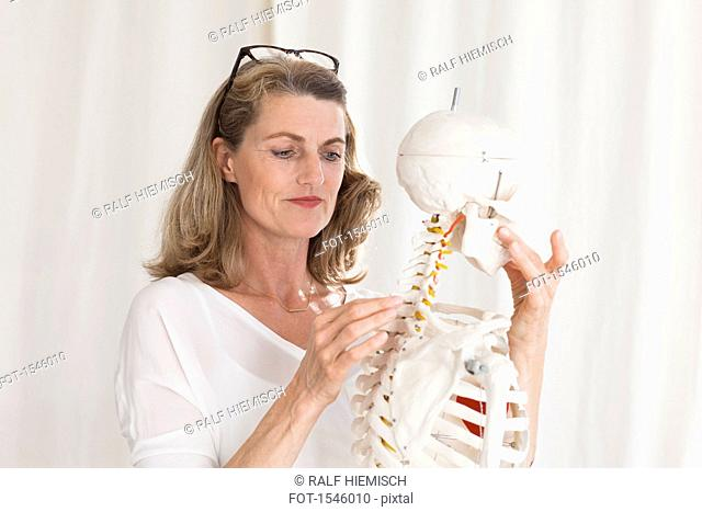 Confident female doctor looking at skeleton while standing in clinic