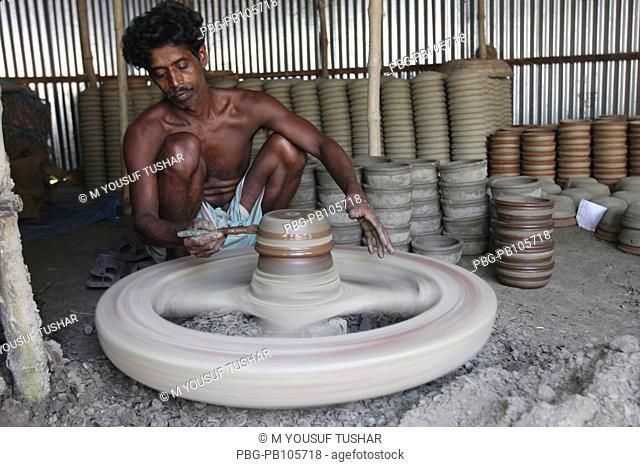 Potter painting to clay pot on spinning wheel Manikganj, Bangladesh September 2009