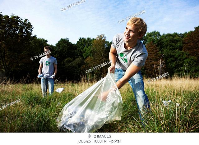 Young man collecting trash in nature