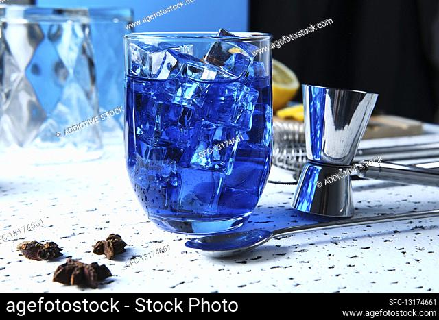 Blue cocktail with ice cubes and barmen tools on table