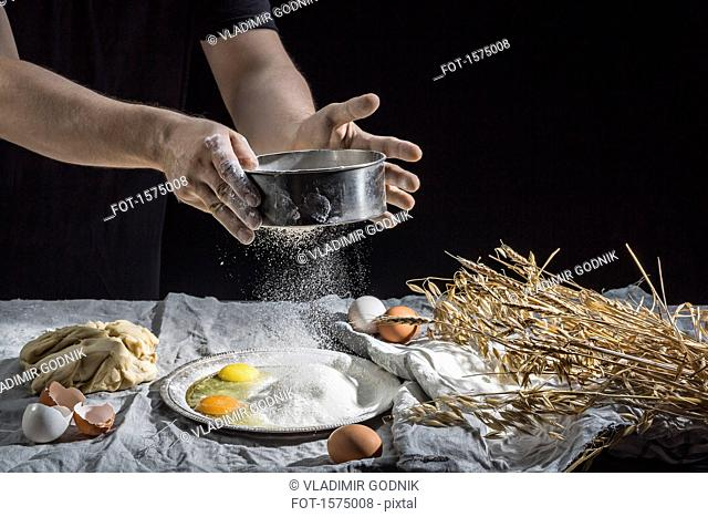 Midsection of man sprinkling flour over eggs at table