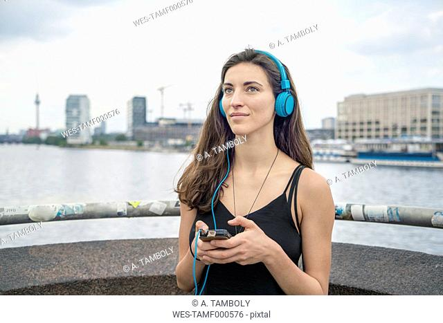 Germany, Berlin, relaxed woman listening music with headphones