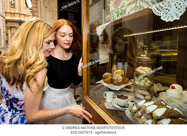 Girls looking through a cake bakery store window
