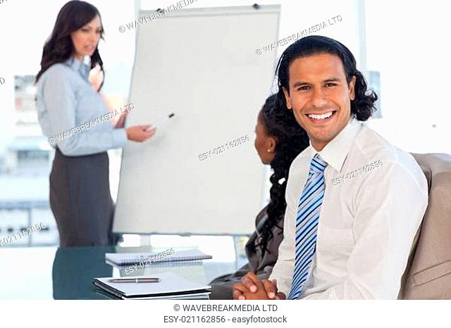 Smiling employee attending a presentation while his team is working behind him