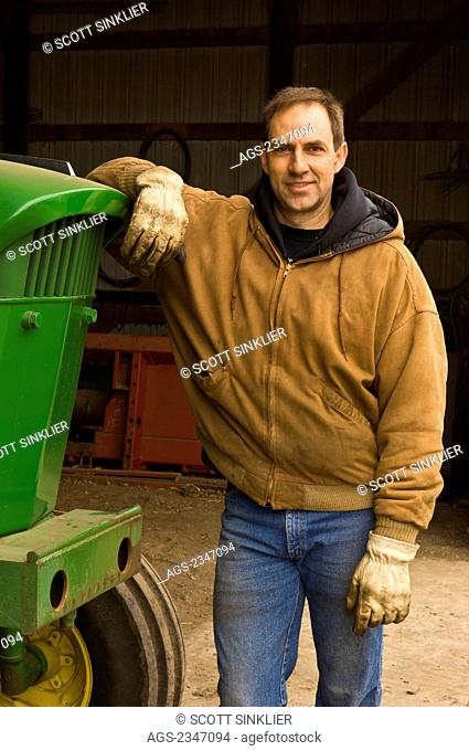 Agriculture - A farmer stands next to his John Deere tractor at the entrance of his workshop prior to spring cultivating and planting / Iowa, USA