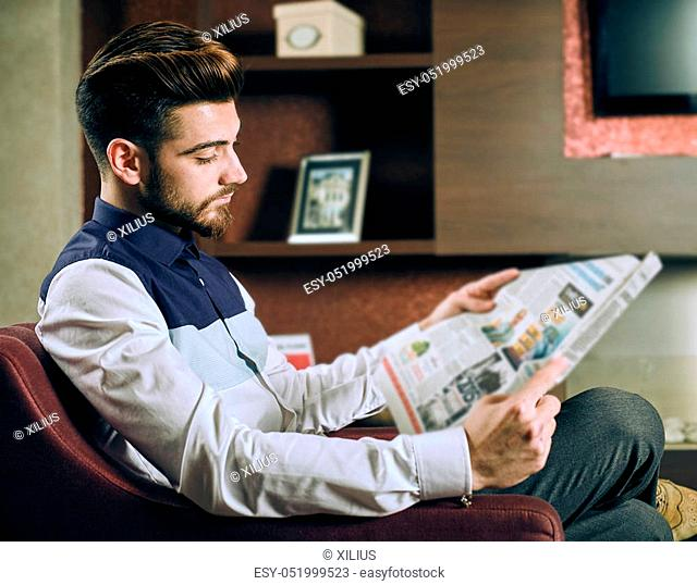 Young elegant man reading newspaper sitting in an armchair