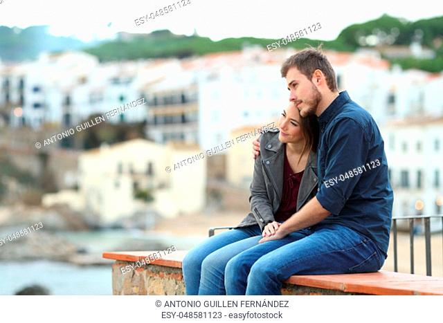 Happy couple in love looking away sitting on a ledge on vacation in a coast town