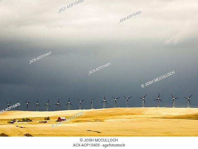 Stormy skies and windmills loom over a farm near Pincher Creek, Alberta, Canada