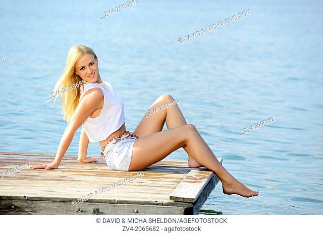 Young woman sitting on a jetty at a lake in Austria