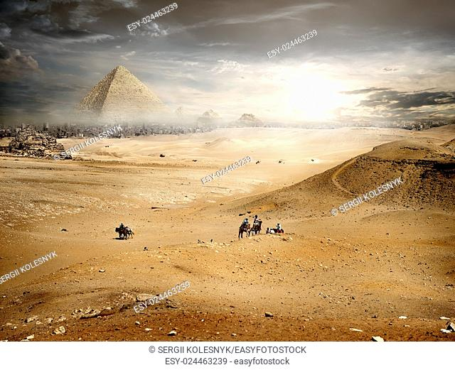 Fog and storm clouds over pyramid in desert