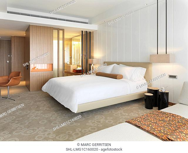 Neat white bed with en suite bathroom in hotel room