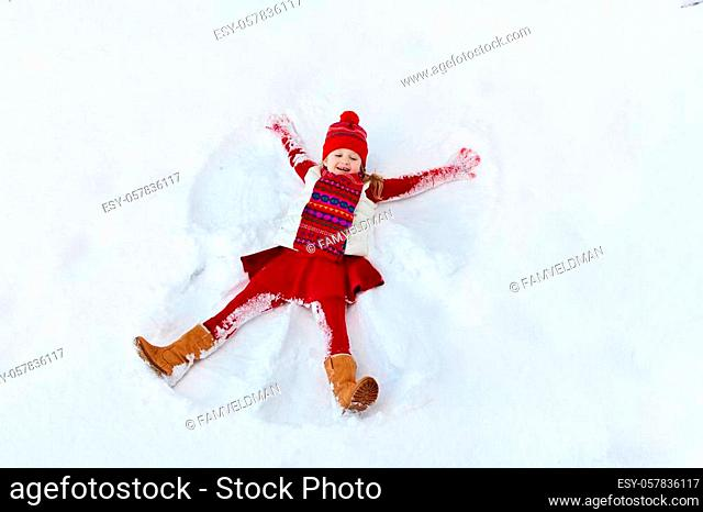 Child making snow angel on sunny winter morning. Kids winter outdoor fun. Family Christmas vacation. Little girl playing in snow after heavy storm