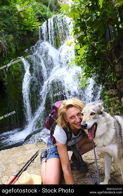 Hiker mature young woman with a dog and waterfall. Tobera, Frias town, Burgos, Castile and Leon, Spain