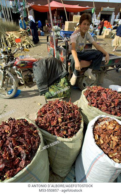 a young uygur man sell dried peppers at kashgar sunday market. kashgar. xinjiang. china. asia