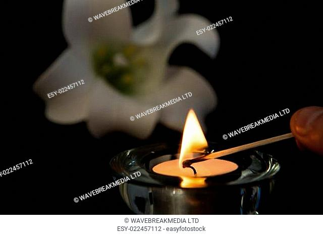 Hand lighting tea light candle with white lily in background symbolising loss