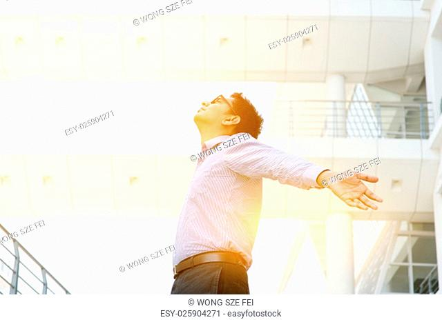 Business freedom concept. Asian businessman arms outstretched enjoying the morning breeze, morning sunlight and modern office as background