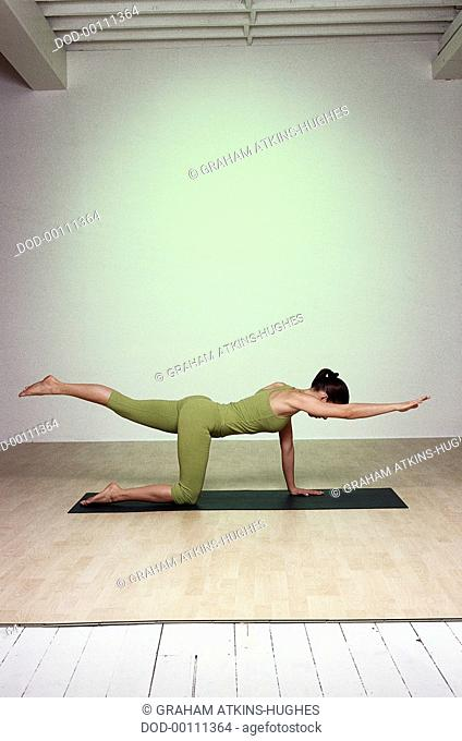 Stay Young, Cat Balance, woman on all-fours on green mat, profile, right knee under hip, stretching raised left leg back, pointing toes away, hips level