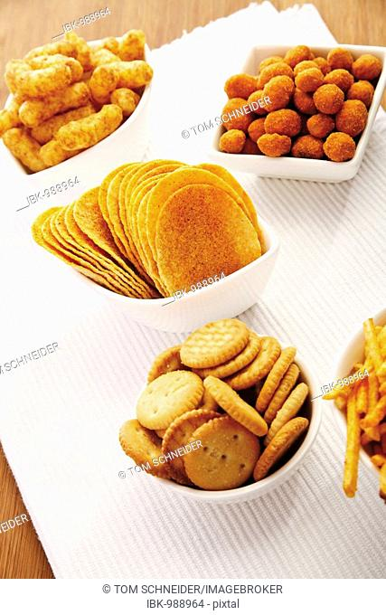 Various spiced snacks in bowls on a table, crisps, peanut flips, potato sticks and salted cookies