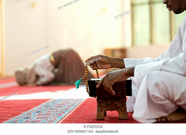 Hand of muslim black man people praying with mosque interior background