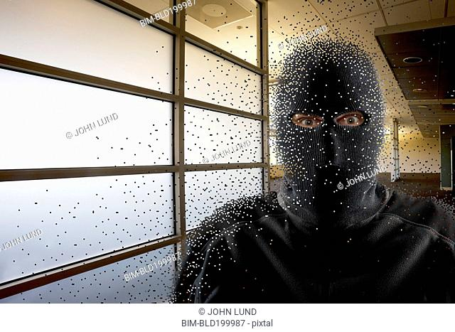 Caucasian man wearing balaclava in office