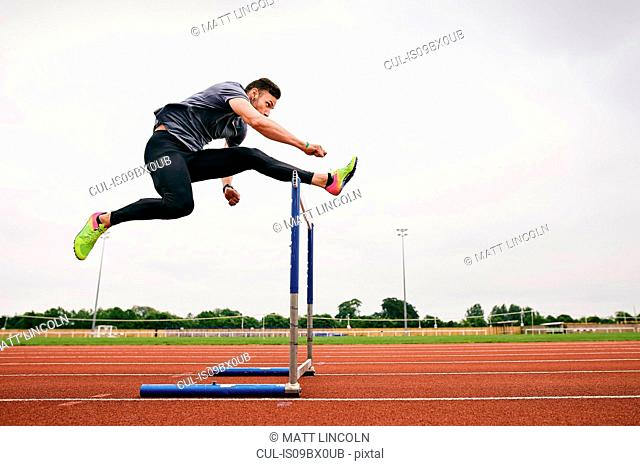 Athlete jumping over hurdle on running track