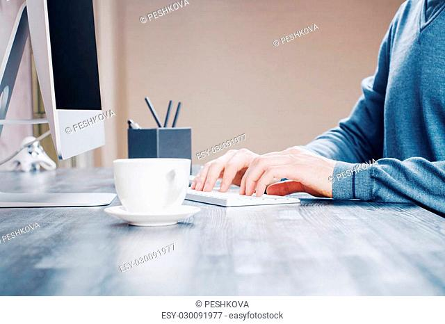 Sideview of desktop with white coffee cup, male hands typing on keyboard and pencil holder