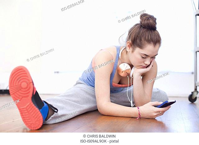 Teenage girl warming up and looking at smartphone in ballet school