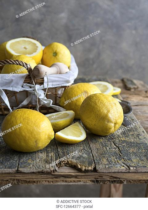 Lemons and citrus reamer placed on wooden board