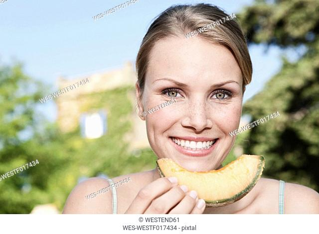 Italy, Tuscany, Magliano, Close up of young woman holding honey melon, smiling, portrait