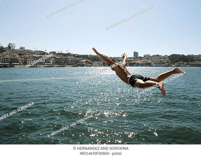 Young man jumping into the water, Porto, Portugal